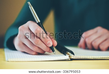 female hands with pen writing on notebook - stock photo