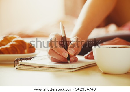 female hands with pen writing on notebook with morning coffee and croissant - stock photo