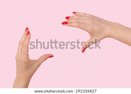 Female hands with red fingernails doing photography gesture against pink background. Nonverbal communication, vision and photography. - stock photo
