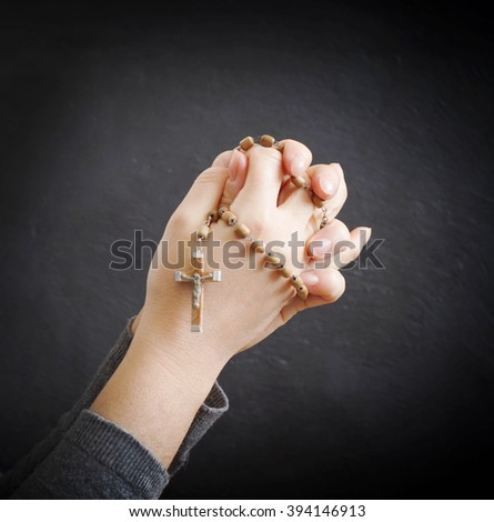 female hands with rosary - stock photo