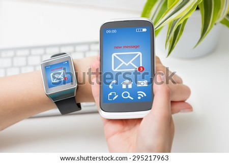 Female hands with smartwatch and phone with email or sms on the screen. - stock photo