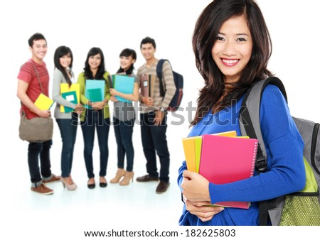 Female happy student carrying bag and books with a group of people at the background - stock photo