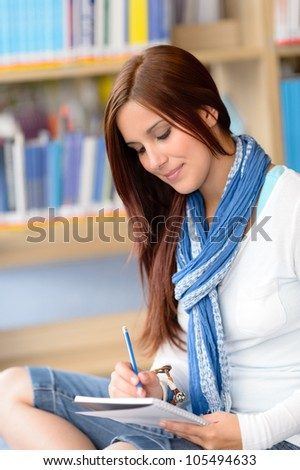 Female high school student at library writing into notepad - stock photo