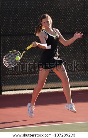 Female High School Tennis Player Hits Forehand Shot - stock photo