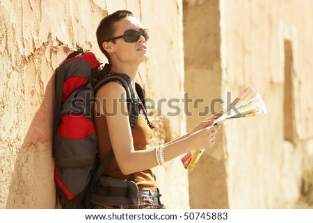 Female hiker holding map, standing by rustic house - stock photo