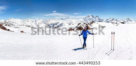 Female hiker in warm bright outfit clothes enjoying trail walk on snow covered track. - stock photo