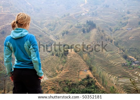 Female Hiker is looking over Rice paddys in Vietnam - stock photo