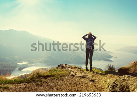 Female hiker on top of the mountain enjoying valley view, Ben A'an, Loch Katrina, Highlands, Scotland, UK - stock photo