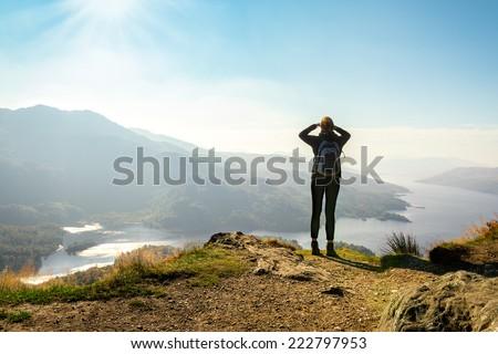 Female hiker on top of the mountain enjoying valley view, Ben A'an, Loch Katrina, Highlands, Scotland, UK - stock photo