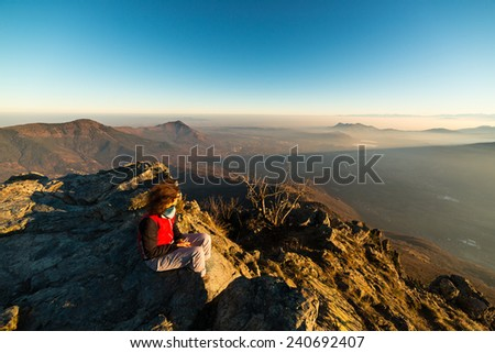 Female hiker reaching her goal at the mountain top and looking at majestic panoramic view of the italian western Alps with foggy valley below. Wide angle view at sunset in winter season. - stock photo