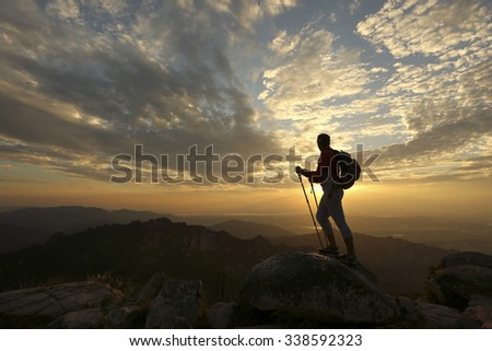 Female hiker reaching the summit of a mountain and watching the sun set over a beautiful landscape with an orange  sky silhouetting her in a dramatic way.  - stock photo