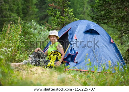 female hiker sitting  in near camp tent and looking at camera - stock photo