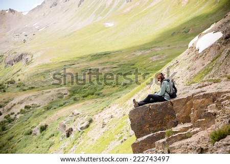 Female Hiker Sitting On Cliff - This is a shot of a young woman hiker sitting down on a cliff enjoying the view of her hike.  - stock photo