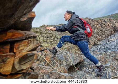 Female hiker using ropes to climb sea cliffs in Devon, England. - stock photo