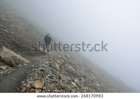 female hiker with a backpack on a highland alpine trail in heavy fog, view from the back - stock photo