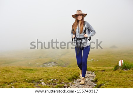 Female hiker with backpack and hat on a mountain trail - stock photo