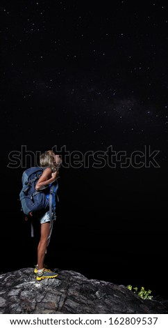 Female hiker with backpack standing on top of a mountain and looking at night sky with stars - stock photo
