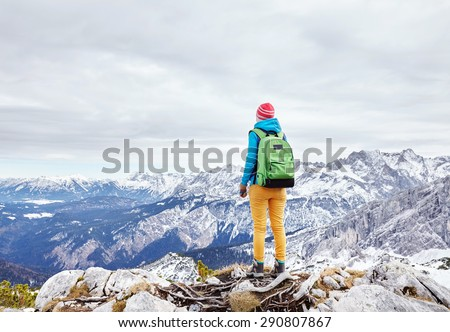 Female hiker with backpack standing on top of mountain - stock photo