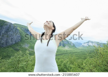 Female hiker with backpack walking and smiling on a country trail - stock photo