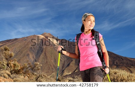 Female hiker. Young asian female model hiking / backpacking in very scenic and beautiful volcanic landscape on the volcano, Teide, Tenerife, Spain. - stock photo