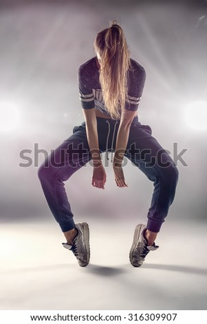 Female Hip Hop Dancer in Tip Toe Position with her Hair Covering her Face Against Brown Wall Background In the Studio. - stock photo
