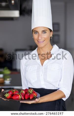 Female hispanic chef holding a plate of strawberries - stock photo