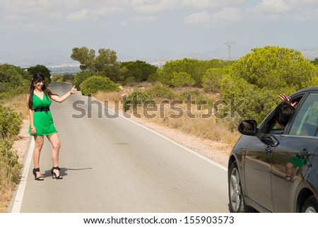 Female hitchhiker being successful in stopping a car - stock photo