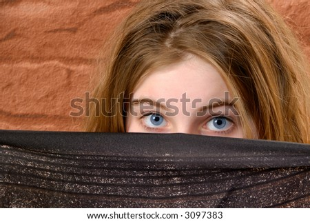 Female holding a dark scarf over her lower face showing her blue eyes - stock photo