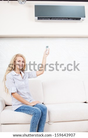 Female holding a remote control air conditioner at home. Happy young woman on sofa - stock photo