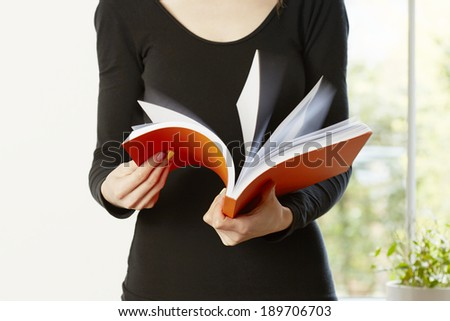 Female holding and flicking through orange book reading. Student education concept - stock photo