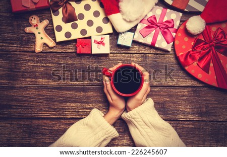Female holding cup of coffee on wooden table near christmas gifts - stock photo