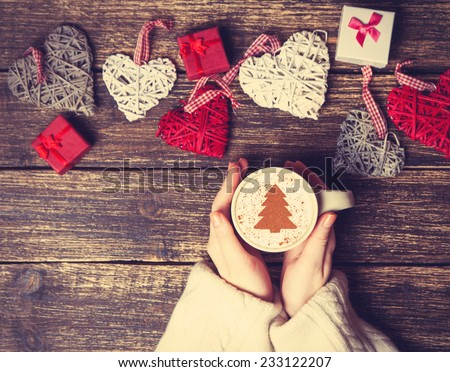 Female holding cup of coffee with cream christmas tree on a table. - stock photo