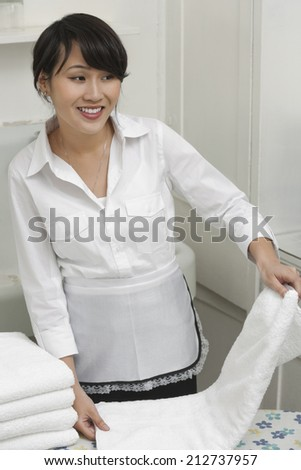 Female housekeeper looking away while folding white towel - stock photo