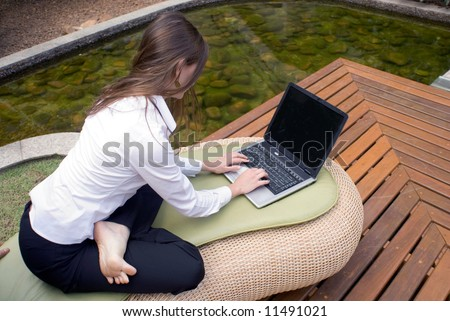Female in business attire working on her laptop while seated outside - stock photo