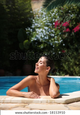 Female in pool smiling with flowers in background - stock photo