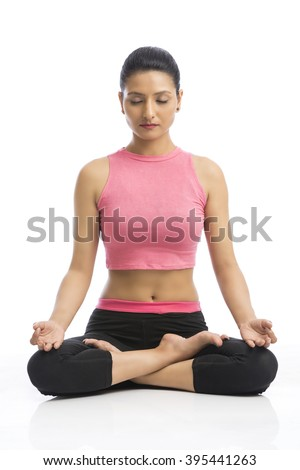 female Indian young doing meditation against white background - stock photo