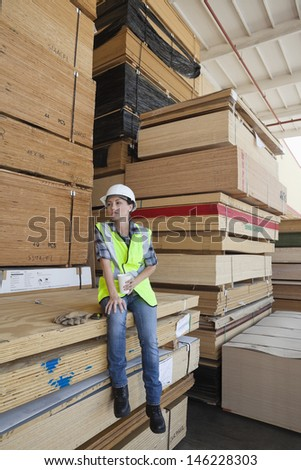 Female industrial worker having coffee while sitting on stack of wooden planks - stock photo