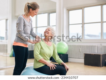 Female instructor assisting senior woman exercising in health club. Older woman assisted by personal trainer at gym. - stock photo