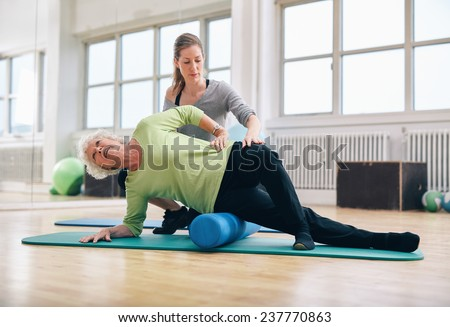 Female instructor helping senior woman using a foam roller for a myofascial release massage at gym. - stock photo