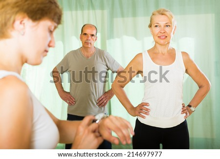 Female instructor keeping eye at training positive mature couple in gym - stock photo