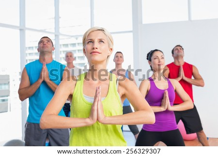Female instructor with class meditating in fitness club - stock photo