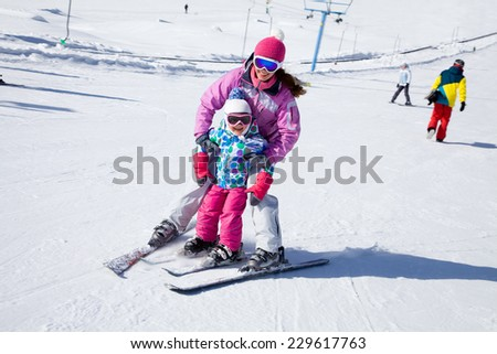 Female instructors teach a child skiing on winter resort - stock photo