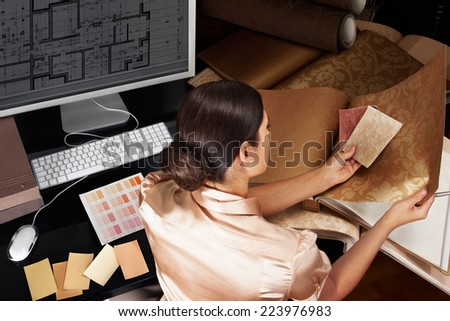 Female interior designer at her workplace. Architectural house plan at computer monitor - stock photo