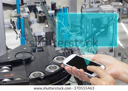Female is holding the smart phone Blank transparent rectangle radiates from the screen smart phone. The rectangle is ready for your text. The automatic production line is in the background.  - stock photo