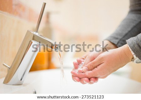 female is washing hands with tap water in bathroom, shallow depth of field - stock photo