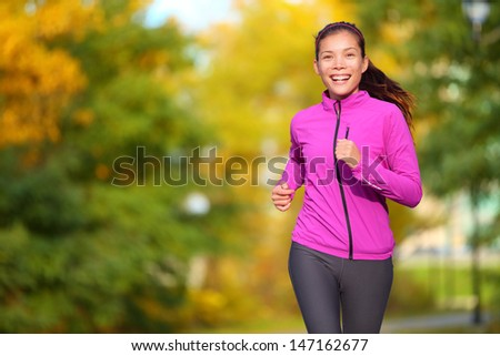 Female jogger. Fit young Asian woman jogging in park smiling happy running and enjoying a healthy outdoor lifestyle. Fitness runner girl in autumn forest with fall foliage. Mixed race Asian Caucasian. - stock photo