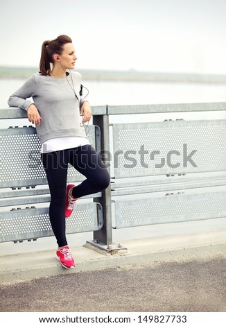 Female jogger resting while listening to mp3 music - stock photo