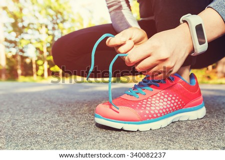 Female jogger tying her running shoes preparing for a jog - stock photo