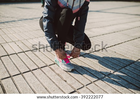 Female jogger tying her running shoes preparing for a jog outdoors - stock photo