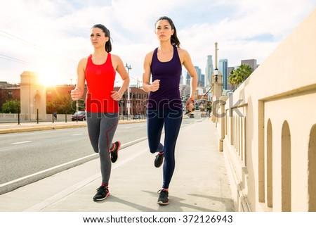Female joggers run on bridge street fitness downtown urban city strong confident thin toned sunrise - stock photo